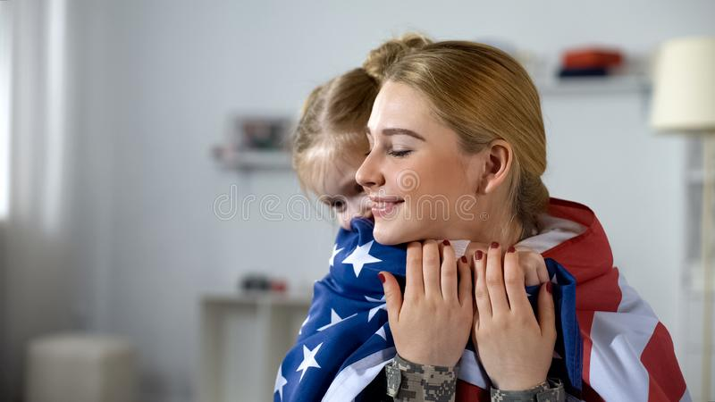 Little daughter hugging soldier mother with US flag, happy with homecoming stock photos