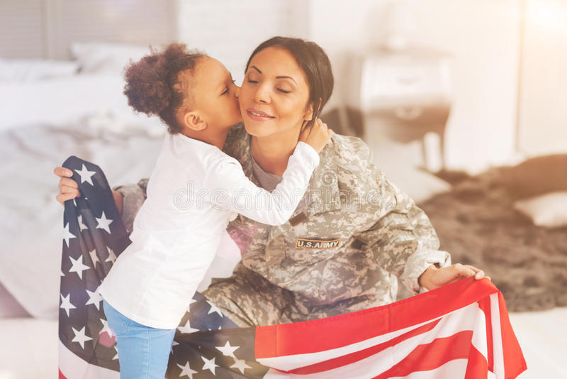Little daughter kissing her mother holding US flag. Loving kiss. Sweet little girl kissing her mother in a uniform of US army while she squatting and holding a stock photos