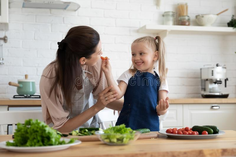 Daughter feed mother gives her tasting cherry tomato cooking together stock photos
