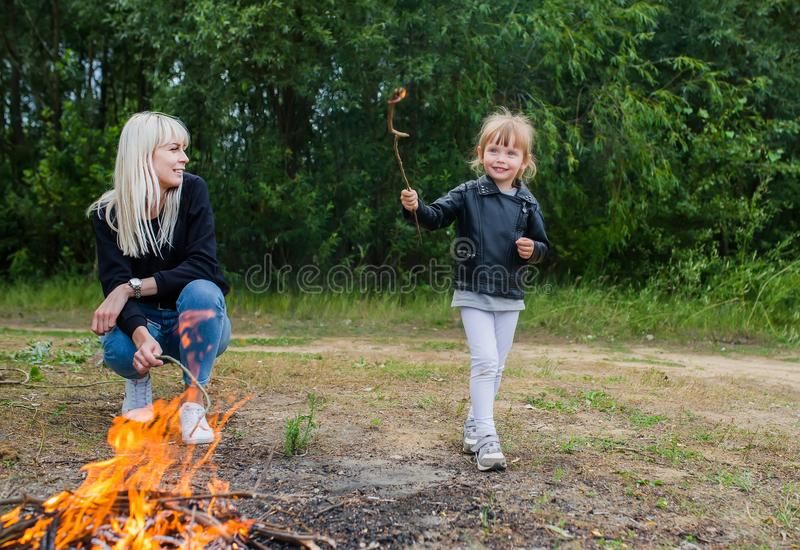 Little daughter with mother cook food on a fire. Family picnic stock photos