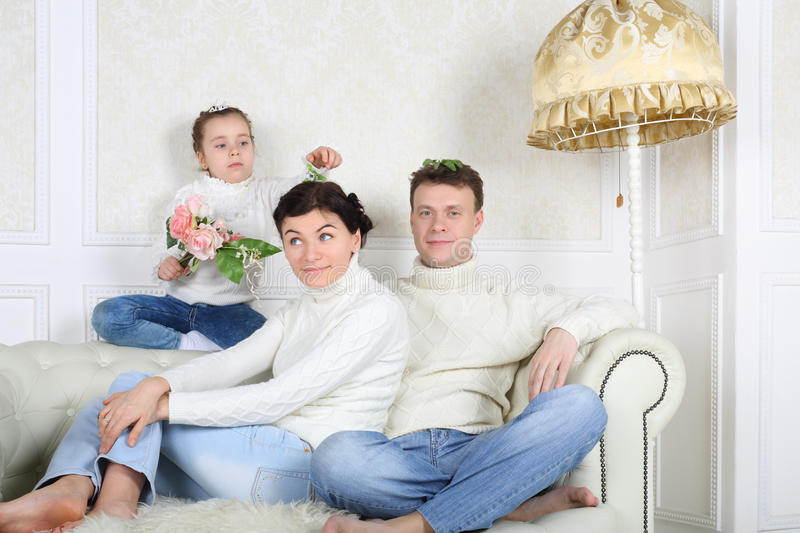 Little daughter puts leaves to heads of mother and father. Little daughter puts artificial leaves to heads of mother and father on white sofa at home stock image