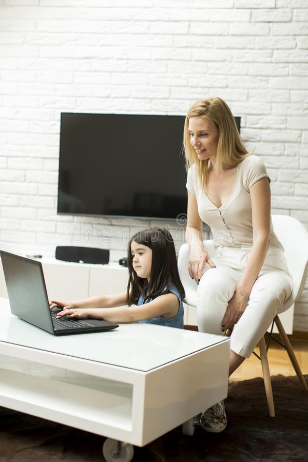 Little daughter sits on the floor and use a laptop. While mother sits next to her on the chair and watches royalty free stock photography