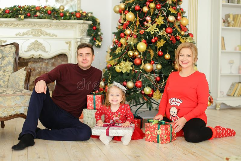 Little daughter sitting with father and pregnant mother near Christmas tree and keeping gifts. stock photography