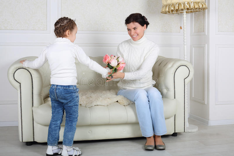 Little daughter takes flowers to smiling mother sitting on sofa. At home stock image