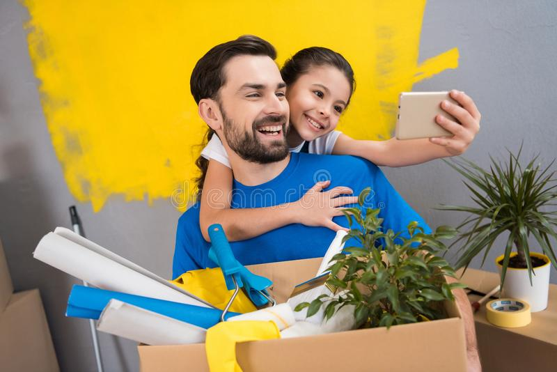 Little daughter using smartphone does selfie with her father who keeps box of tools and things. Family does house repairs together stock images