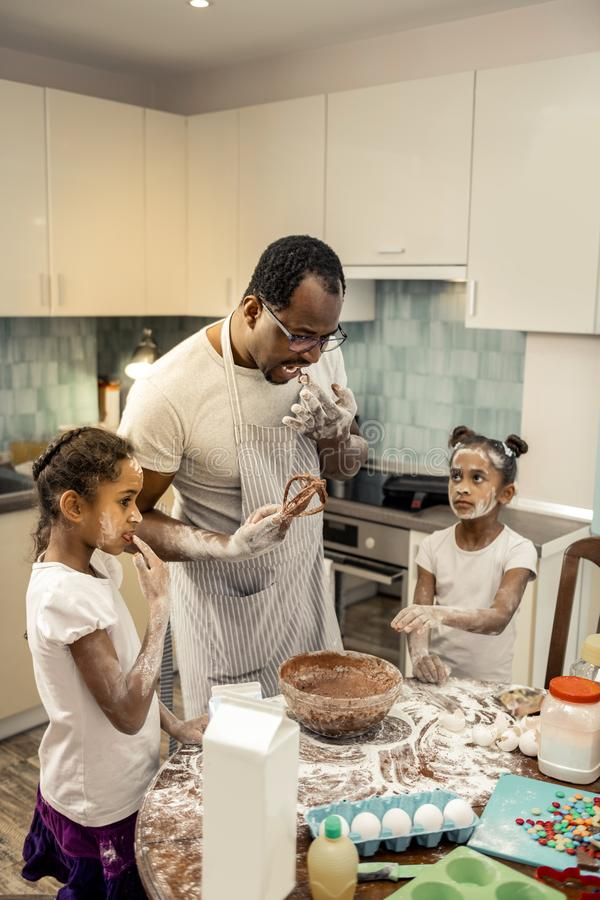 Little daughters having their faces in flour cooking with father. Faces in flour. Little cute dark-haired daughters having their faces in flour cooking with stock images