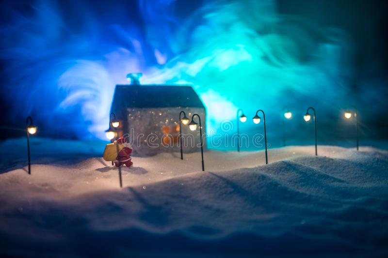 Little decorative cute small houses in snow at night in winter, Christmas and New Year miniature house in the snow at night with stock photo