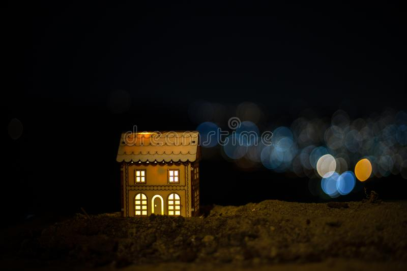 Little decorative house, beautiful festive still life, cute small house at night, Night city real bokeh background, happy winter royalty free stock image