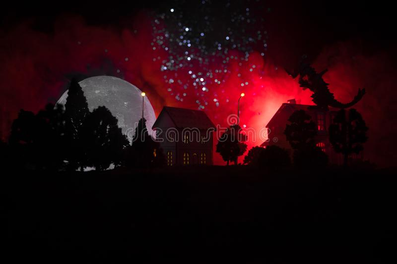 Little decorative houses, cute small houses at night, pine trees glowing lights, and horror big monster at the street. Horror. Halloween concept. Selective stock image