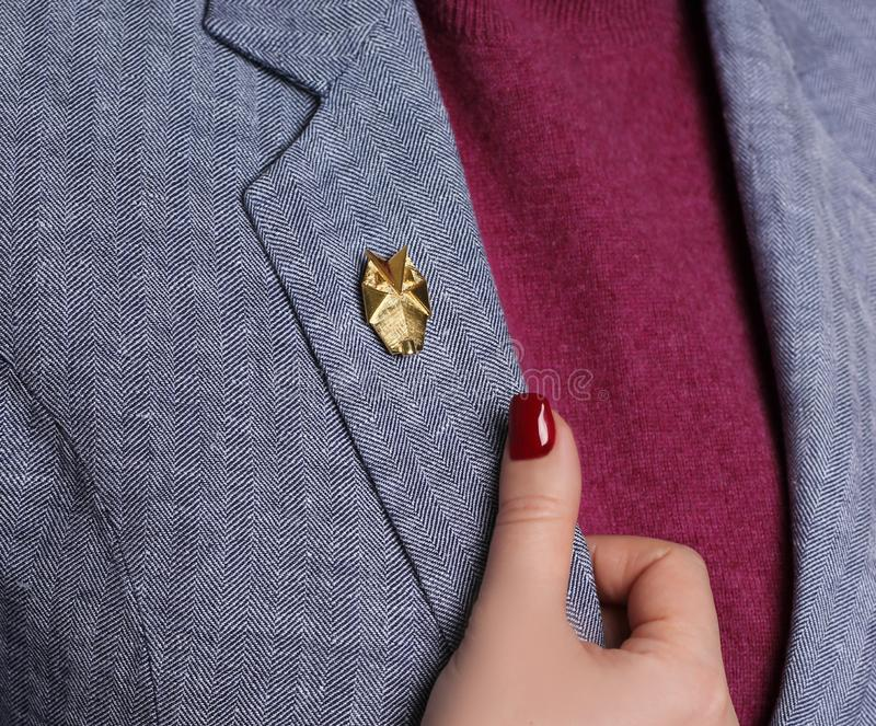 Little designer brooch closeup on the jacket of a young girl royalty free stock photo