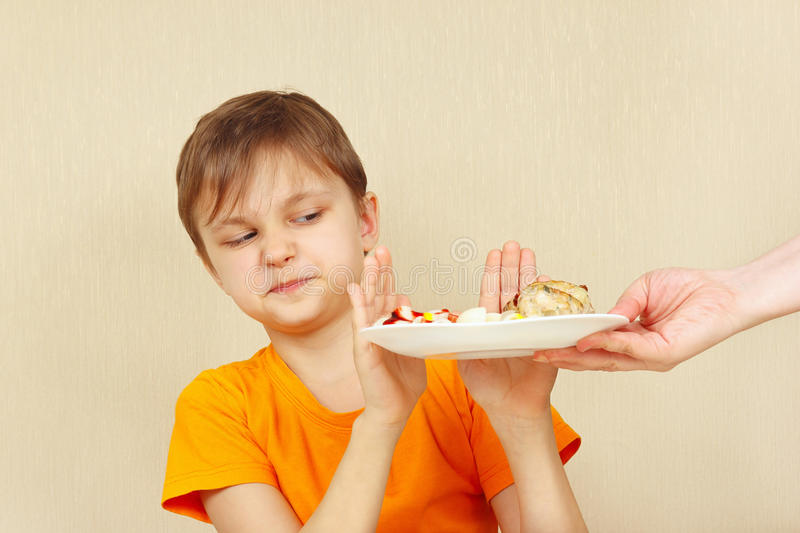 Little displeased boy refuses to eat pasta with cutlet. Little displeased boy refuses to eat a pasta with cutlet royalty free stock photography