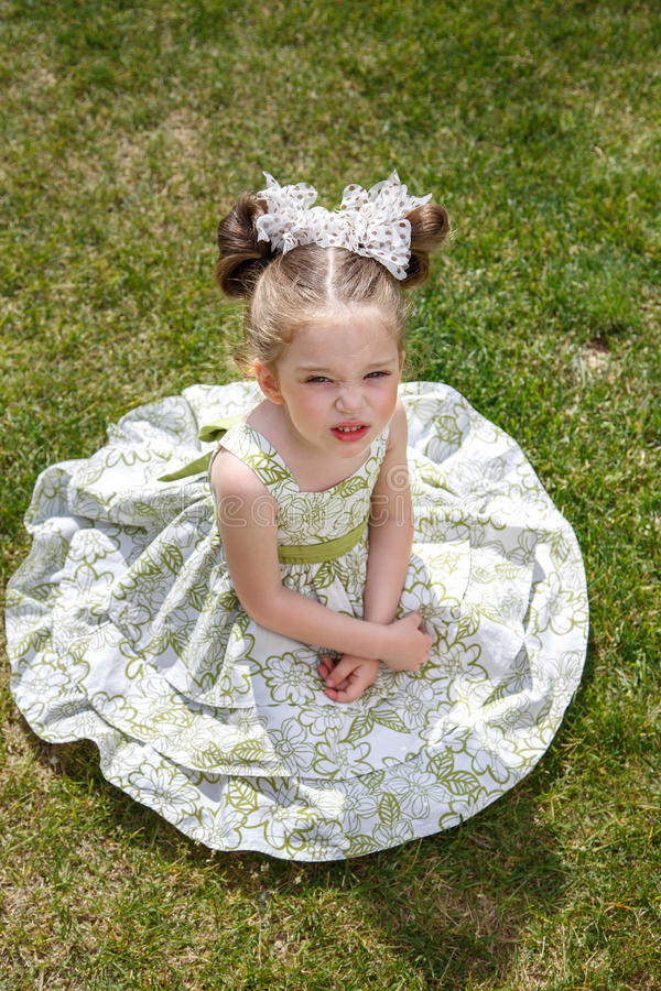 Little dissatisfied girl. In a dress with two bows sitting on the grass. her face unhappy. Girl tired. top view stock photography
