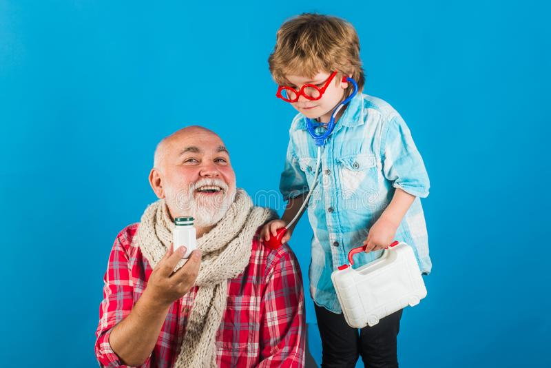 Little doctor giving grandfather medicament. Man in knitted colorful scarf with medicine. Smiling grandfather and his. Grandson playing with a stethoscope stock images