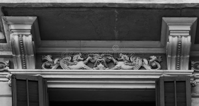 Little dragons protecting the goat´s head. Shot in black and white detail on the facade of this historic building representing some character, animal or stock photo