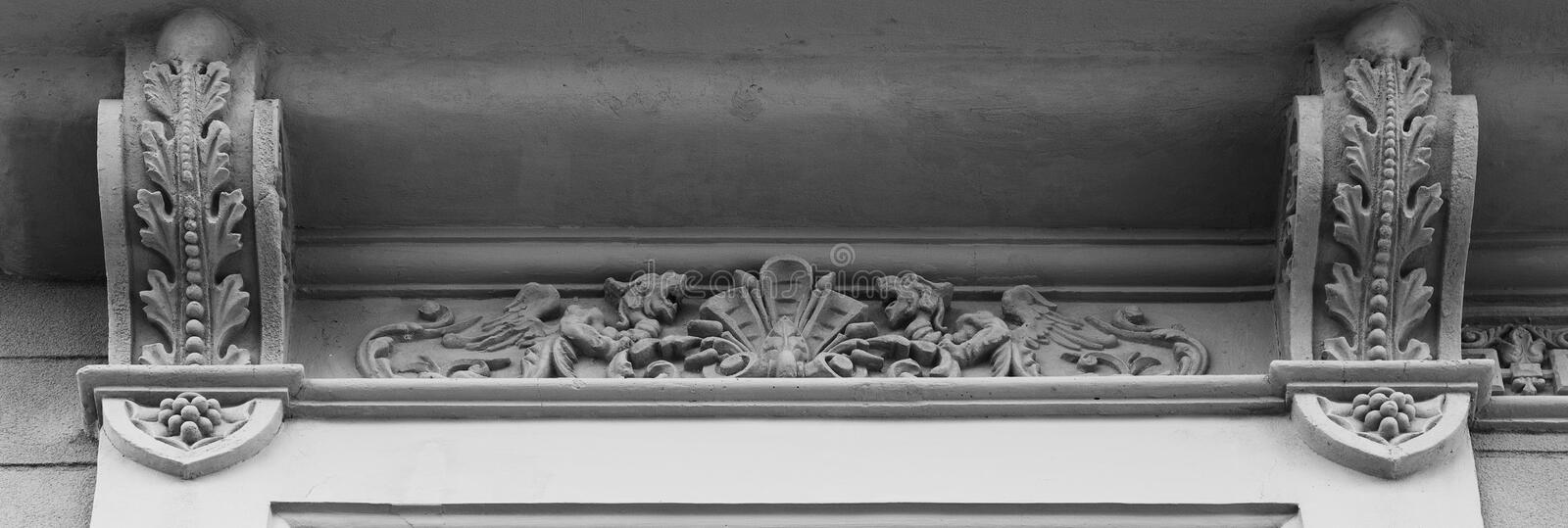 Little dragons protecting the shield. Shot in black and white detail on the facade of this historic building representing some character, animal or flower. Set stock image