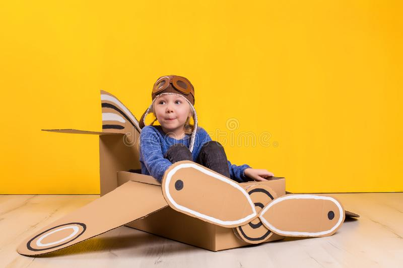 Little dreamer girl playing with a cardboard airplane. Childhood. Fantasy, imagination. Studio photography on a yellow background. Imagination or exploration stock photography