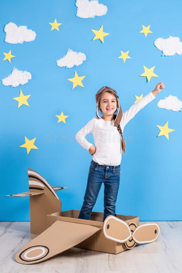 Little dreamer girl playing with a cardboard airplane at the studio with blue sky and white clouds background. stock photography