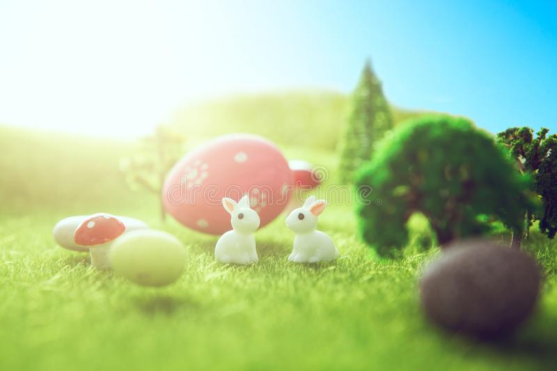 Little Easter bunny toys and Easter eggs on a green grass. Yellow easter egg spring meadow with two white rabbit and easter eggs. royalty free stock photos