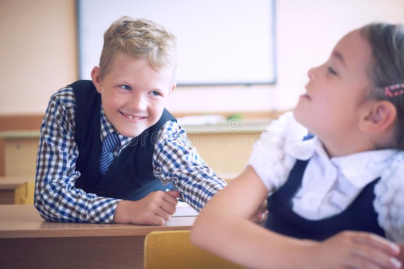 Little elementary school student boy tries to disturb the girl during the lesson. Boy tries to reach the girl`s back.  stock image