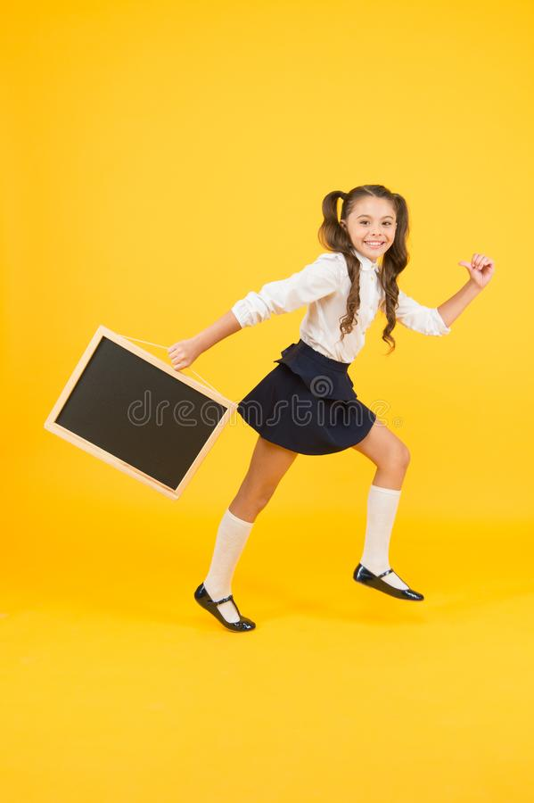 Little and energetic. Little child carrying blackboard on yellow background. Little schoolgirl with black-board for stock photography
