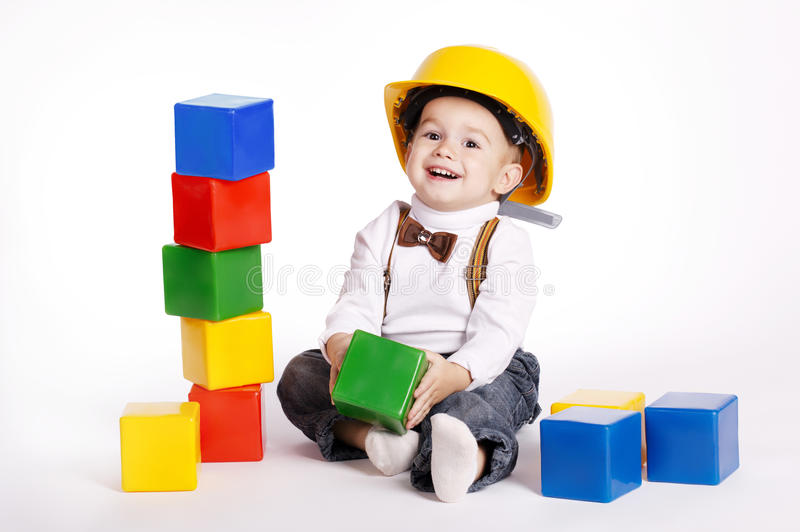 Little engineer with helmet plays with cubes. Little engineer with protective helmet plays with cubes royalty free stock photography