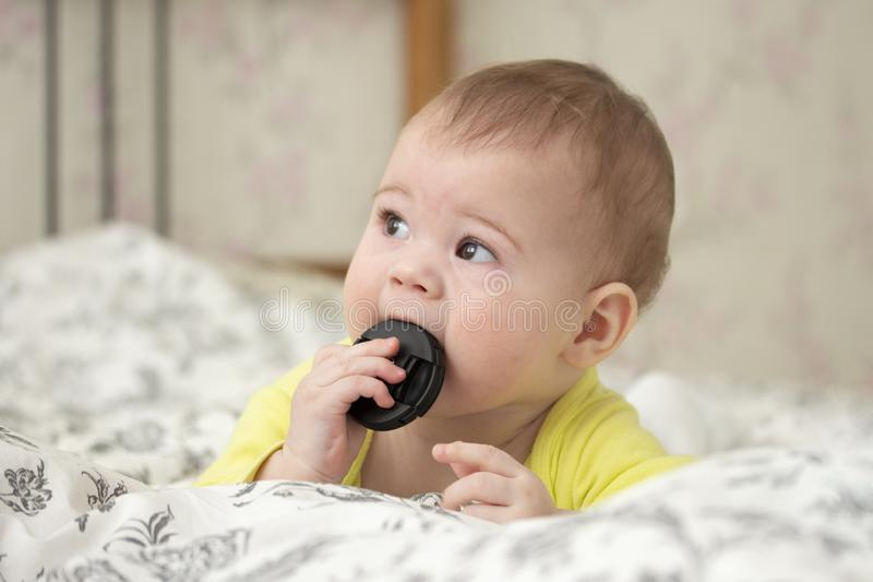 Little European baby girl boy puts in his mouth the cap from the camera lens. A novice photographer for 7 months lies on the bed royalty free stock images