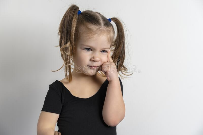 Little european girl on a light background with a dreamy facial expression. Hand in the face in a pensive pose royalty free stock photos