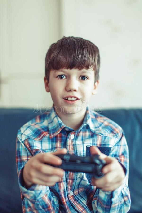 Little excited kid playing video game stock photos