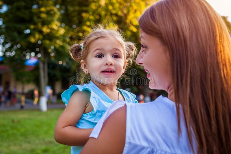 Little excited toddler girl smiling outdoors. Mother holding her daughter on hands in park. royalty free stock images