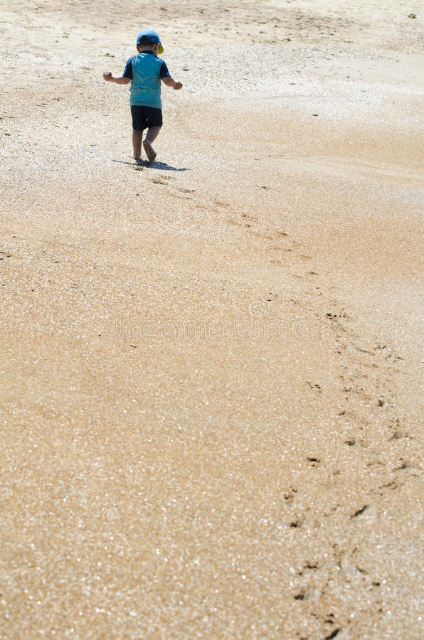 The little explorer. Footsteps on a sandy beach / The little explorer (Horizontal royalty free stock image