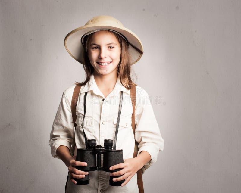 Little explorer holding binoculars. On a gray background stock images