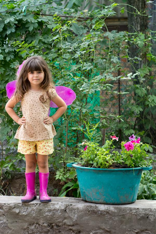 Little fairy kid with pink wings playing outdoor. stock photo