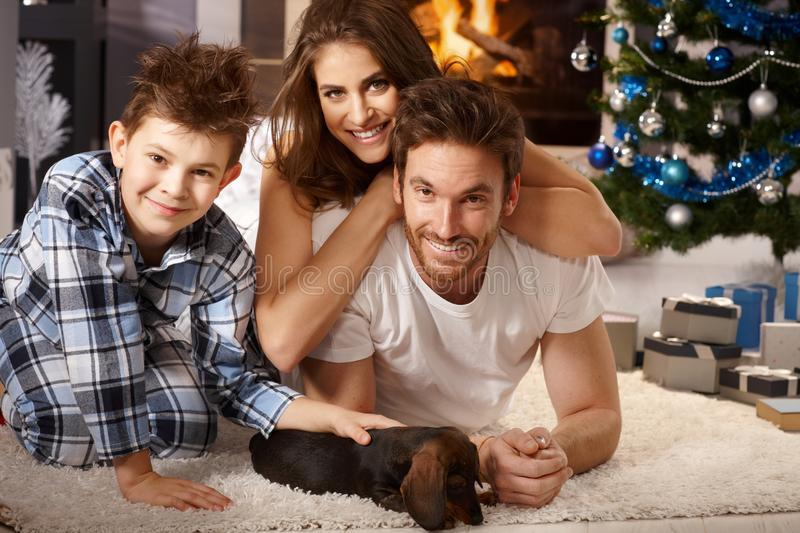 Little family with dog at xmas. Happy little family playing on floor with newly received puppy at christmas time royalty free stock image