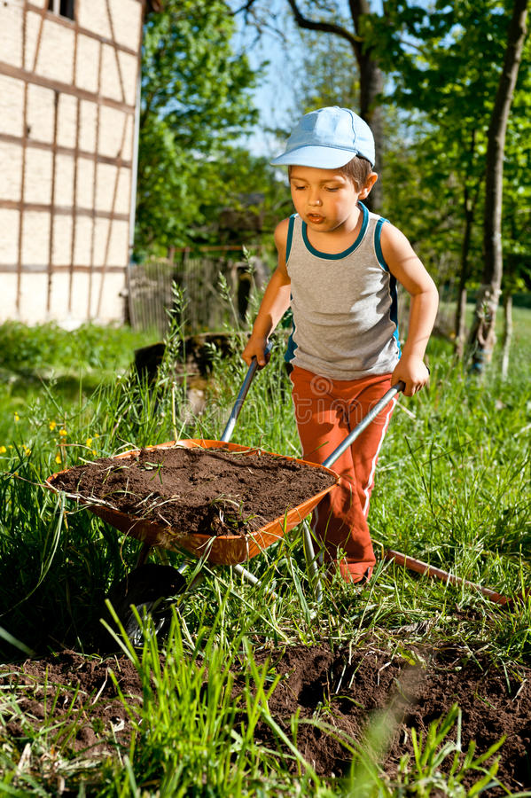 Little farmer with wheelbarrow royalty free stock photo