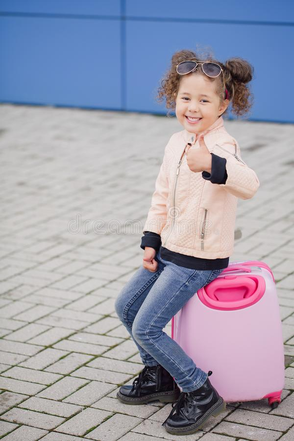 Little fashion curly smiling girl siting on the suitcase. Concept travel stock photography