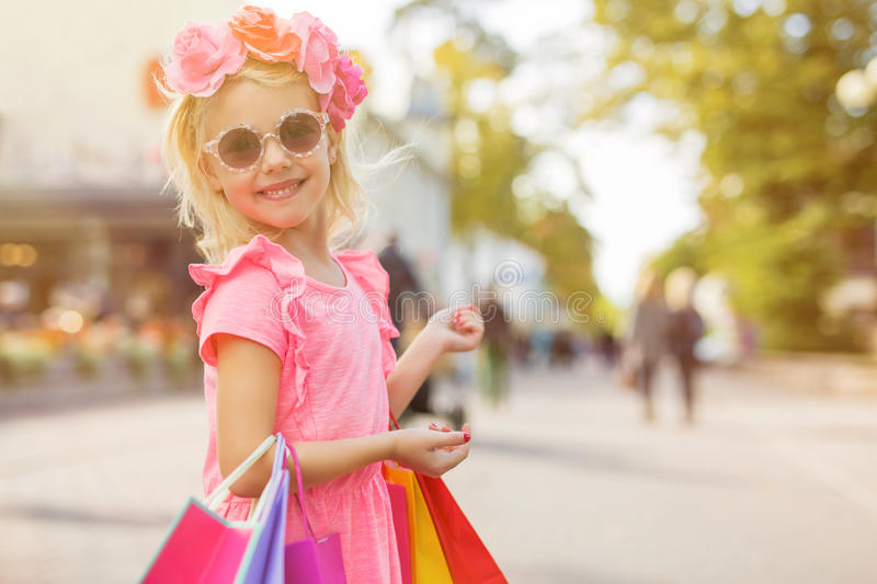 Little fashion girl wearing sunglasses and holding shopping bags royalty free stock photo