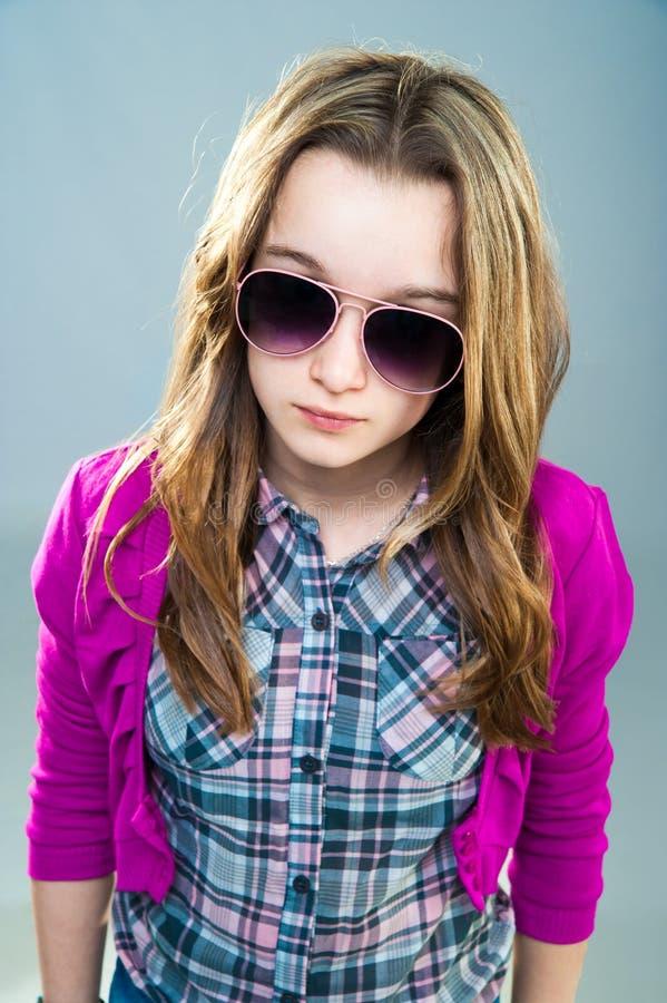 Little fashion model in sunglasses. Beautiful little fashion model in sunglasses on a blue background stock image