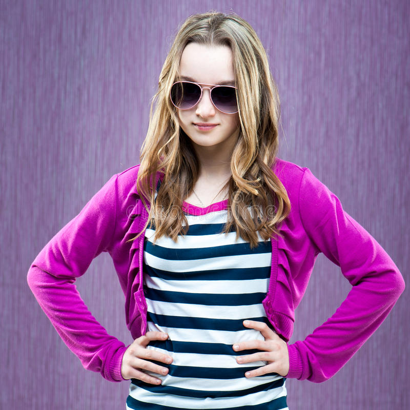 Little fashion model in sunglasses. Beautiful little fashion model in sunglasses on a purple background stock image