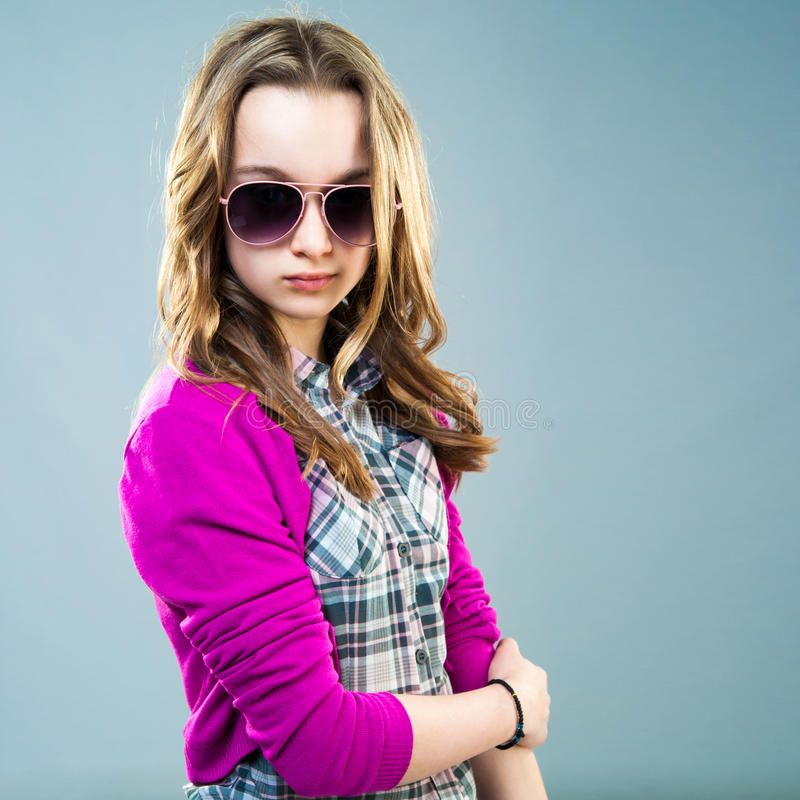 Little fashion model in sunglasses. On a blue background stock photo