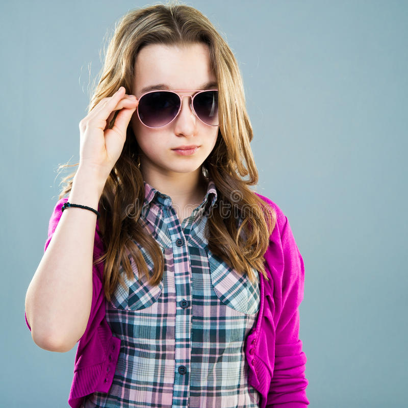 Little fashion model in sunglasses. Portrait of a beautiful little fashion model in sunglasses on a blue background stock image