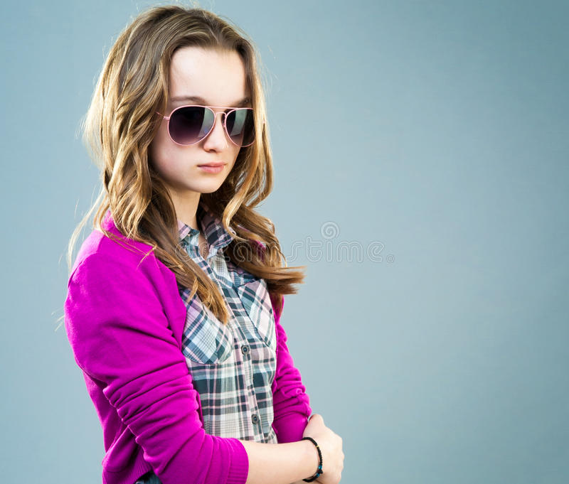Little fashion model in sunglasses. Portrait of a beautiful little fashion model in sunglasses on blue background royalty free stock image