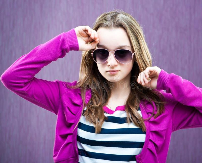 Little fashion model in sunglasses. Portrait of a beautiful little fashion model in sunglasses on purple stock images