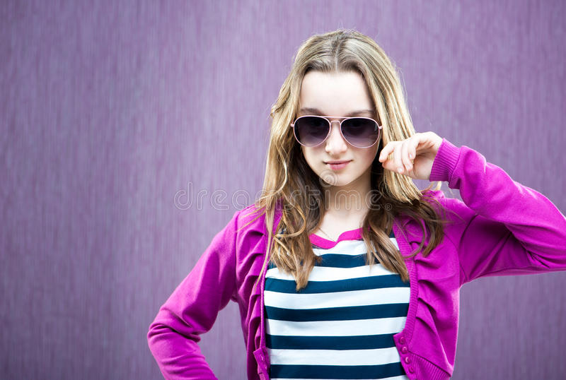 Little fashion model in sunglasses. Portrait of a beautiful little fashion model in sunglasses on purple background royalty free stock photos