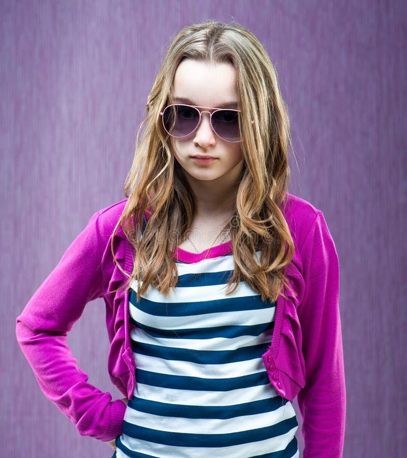 Little fashion model in sunglasses. Portrait of a beautiful little fashion model in sunglasses on a purple background stock photo