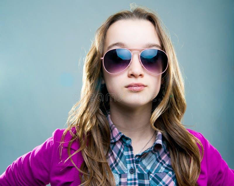 Little fashion model in sunglasses. Portrait of a little fashion model in sunglasses on a blue background stock photos