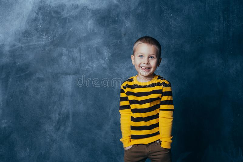 A little boy poses in front of a gray-blue concrete wall. Portrait of a smiling child dressed in a black and yellow striped. Little fashionable boy posing in stock image