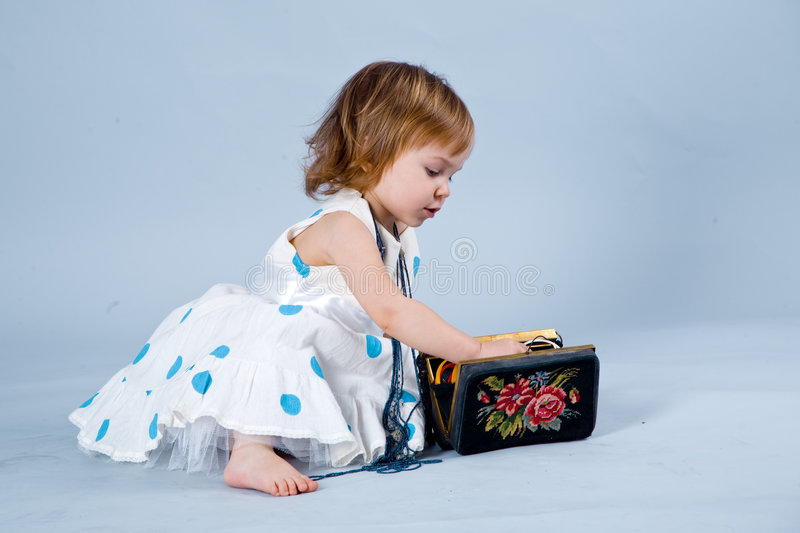 Little fashionable girl. Nice baby girl in beautiful dress playing with handbag with jewellery royalty free stock images