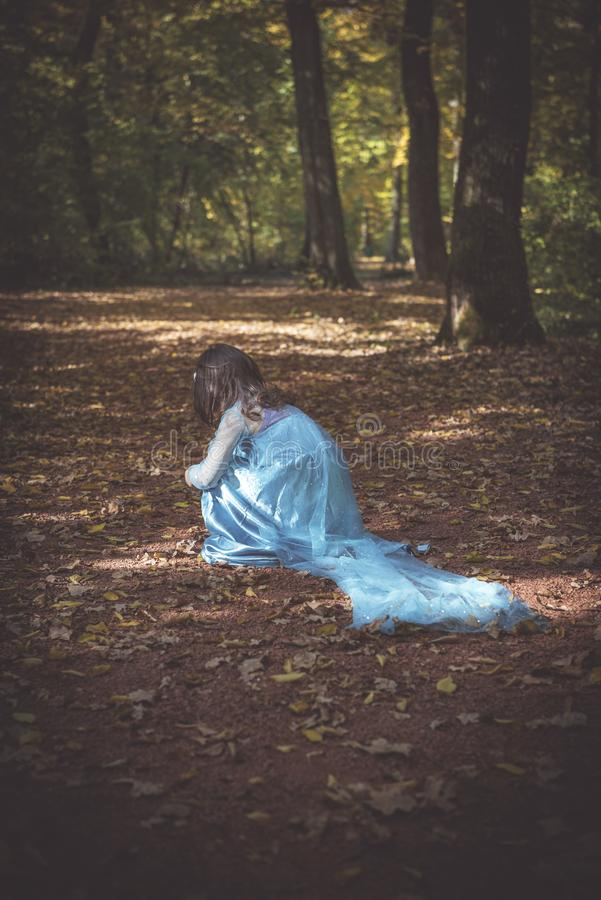 Little fashionable girl. Little alone girl in the dark woods,selective focus royalty free stock photography