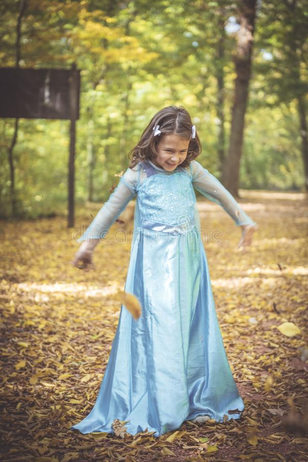 Little fashionable girl. Playful little girl playing in the wood,blurred motion royalty free stock image
