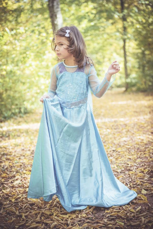 Little fashionable girl. Portrait of beautiful little girl in blue dress stock images